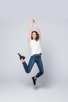 茶色の長い髪と白で隔離されるスタジオでジャンプアップ幸せな笑顔の表情で踊っている女の子