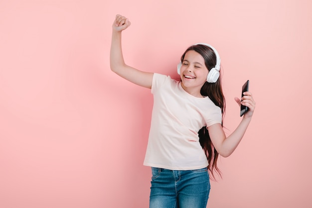 A dancing girl with closed eyes in earphones listening to music with hand up holding telephone