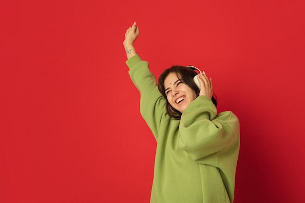 Dancing in headphones. caucasian woman's portrait isolated on red wall with copyspace. beautiful female model in green hoodie. concept of human emotions, facial expression,