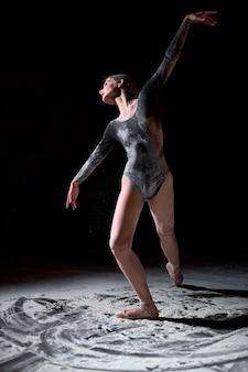 小麦粉の概念で踊る。小麦粉のアスリート女性ダンサー。孤立したスタジオで黒の背景にダンス要素を作る女性。黒のボディスーツはパウダーです。優雅なバレエダンサーの肖像画