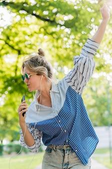Танцуя в парке и слушая музыку, вид спереди