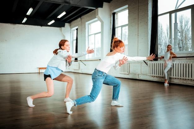 Танцы в студии. красивая рыжая профессиональная танцовщица в синих джинсах и ее ученица выразительно танцуют