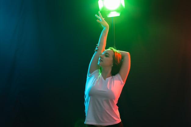 Танцы, джаз-фанк и концепция хип-хопа - молодая женщина танцует в темноте и скрещивает руки над головой.