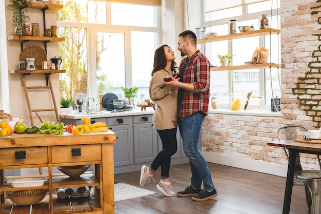 Dancing in kitchen. young romantic couple celebrating engagement copy space. cute young couple dancing at home, drinking wine.