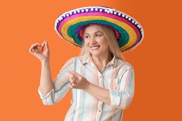 Танцующая зрелая мексиканская женщина в шляпе сомбреро на цветной поверхности
