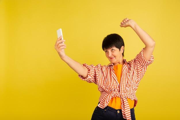 ダンシング。スタイリッシュな衣装、黄色のスタジオの背景に分離された服装の年配の女性の肖像画。技術と楽しい高齢者のライフスタイルのコンセプト。トレンディな色、永遠に若さ。広告のコピースペース。
