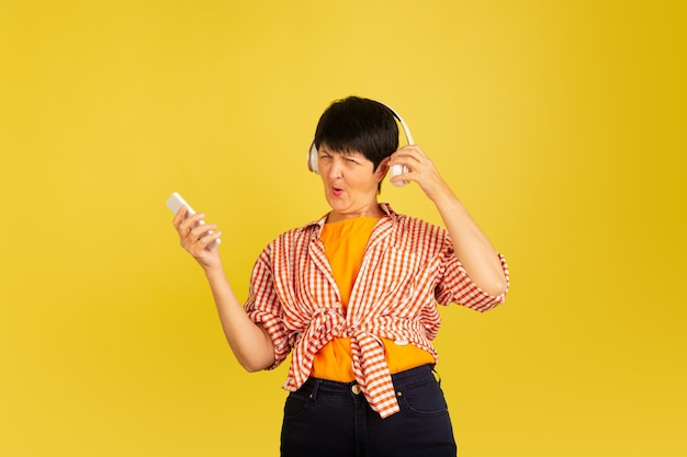 Dancing. portrait of senior woman in stylish outfit, attire isolated on yellow studio background. tech and joyful elderly lifestyle concept. trendy colors, forever youth. copyspace for your ad.