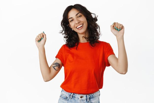 Ragazza queer che balla ridendo, alzando le mani e celebrando il concetto lgbtq del mese dell'orgoglio, divertendosi, in piedi su bianco