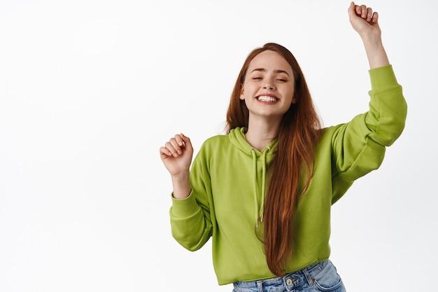 楽しんで、陽気で幸せそうに見え、手を上げて唱え、夏休みを祝い、白の上に立って踊る赤毛の女の子。