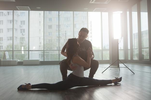 練習中に高度なスキルを示すダンス教師。ダンサー関係。美しいパフォーマンス。