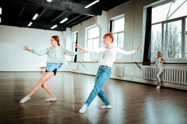 一緒に踊る。ブルージーンズを身に着けている美しい赤毛のプロのダンサーとスタジオで踊っている彼女の学生