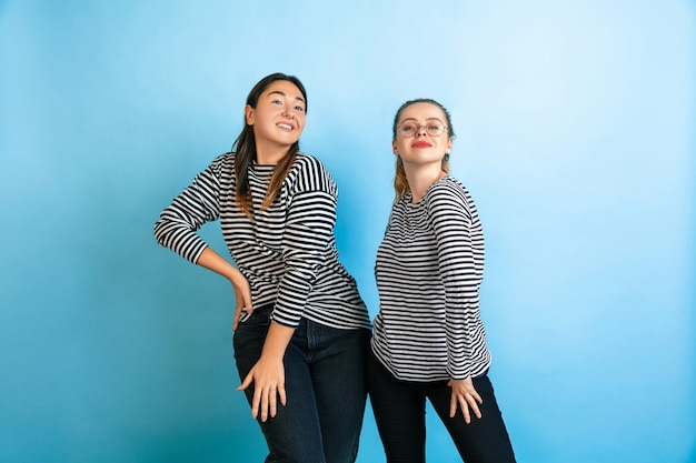 Dancing together. young emotional women isolated on gradient blue studio background. concept of human emotions, facial expession, friendship, ad. beautiful caucasian female models in casual clothes.