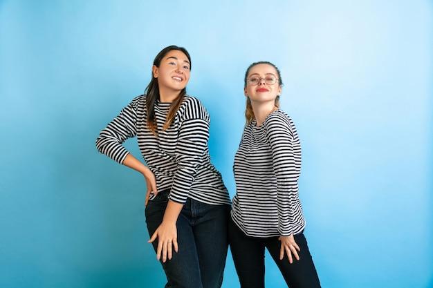 Танцы вместе. молодые эмоциональные женщины, изолированные на градиентном синем фоне студии. понятие человеческих эмоций, выражение лица, дружба, реклама. красивые кавказские женские модели в повседневной одежде.