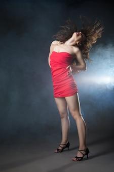 Танцующая женщина в красном платье на черном фоне