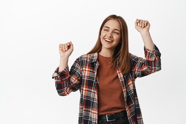踊る女性、学生のパーティー、パーティーで楽しむ、手を上げる、笑って幸せな笑顔、イベントを楽しむ、音楽に合わせて踊る、白い壁に立つ