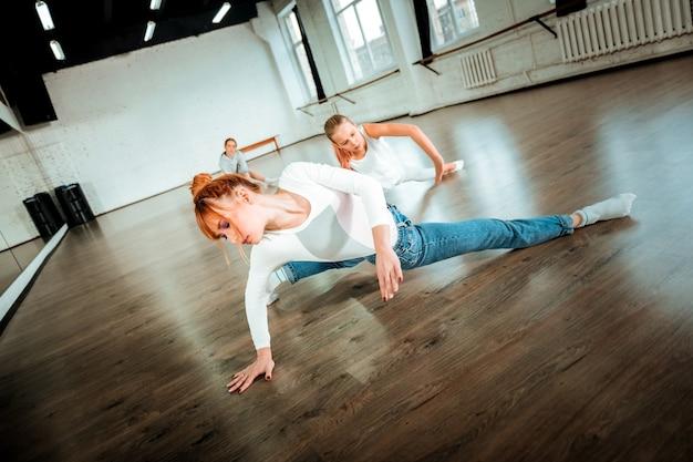 ダンストレーニング。複雑なダンスの動きをしている白い服を着ているプロのバレエ教師と彼女の学生