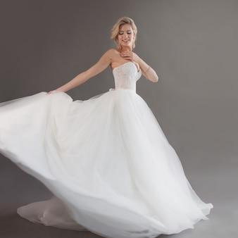 고급스러운 웨딩 드레스에 젊은 신부 춤. 흰색에서 예쁜 여자입니다. 행복, 웃음과 미소의 감정, 회색 배경