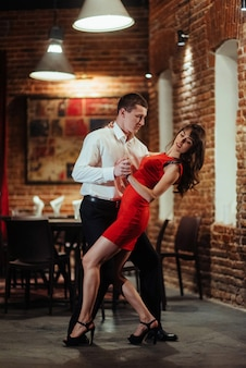 白い背景の上の若いカップルのダンス。情熱的なサルサ。