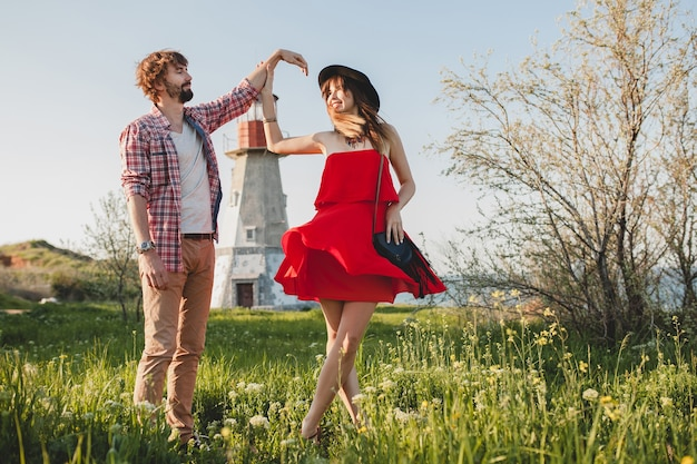 田舎、インディーヒップスターのボヘミアンスタイル、週末の休暇、夏の服装、赤いドレス、緑の芝生、手をつないで恋にスタイリッシュなカップルを踊る