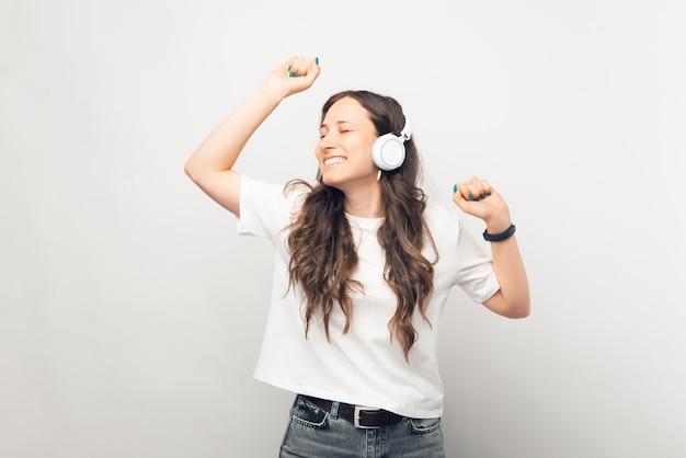 踊っている若い女性が白い背景で音楽を聴いています。