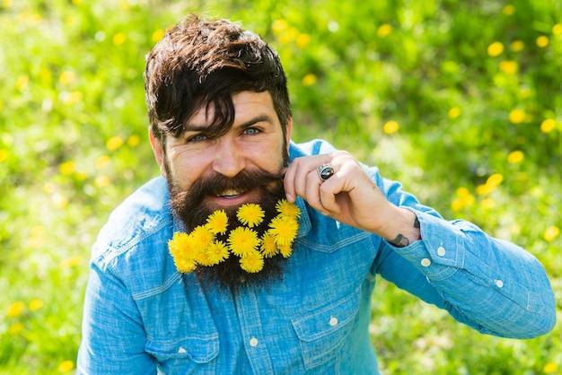 タンポポ。床屋と美容師。花のファッションと美しさ。あごひげを生やしたヒップスターは晴れた日をお楽しみください。ひげの髪に花を持つ幸せな男。はげと脱毛の概念。夏と春の季節。