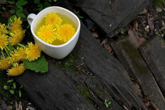 흰색 컵에 민들레 꽃 차 주입을 닫습니다. 초본 음료, 노란 꽃과 잎 tisane