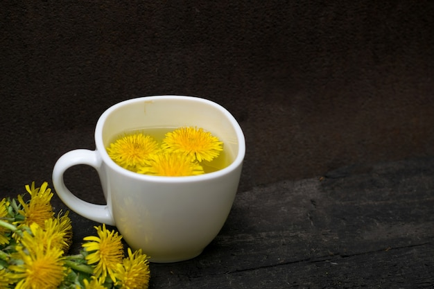 Dandelion flower tea infusion in white cup close up. herbal beverage, yellow flowers and leaves tisane on natural dark background
