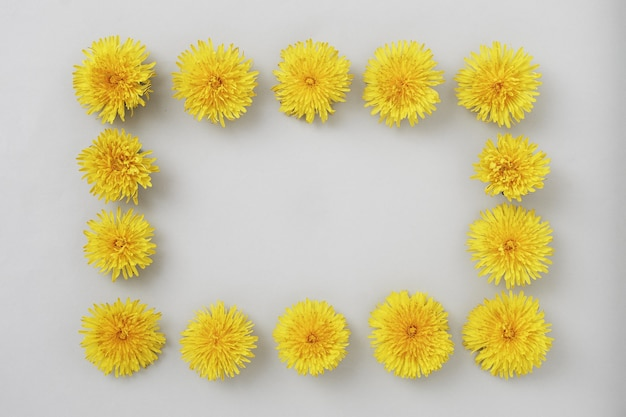 タンポポの花は、招待状やバナーテキスト用のコピースペースで灰色の背景に囲まれています。春のミニマルコンセプトコンセプトとフラットレイ。