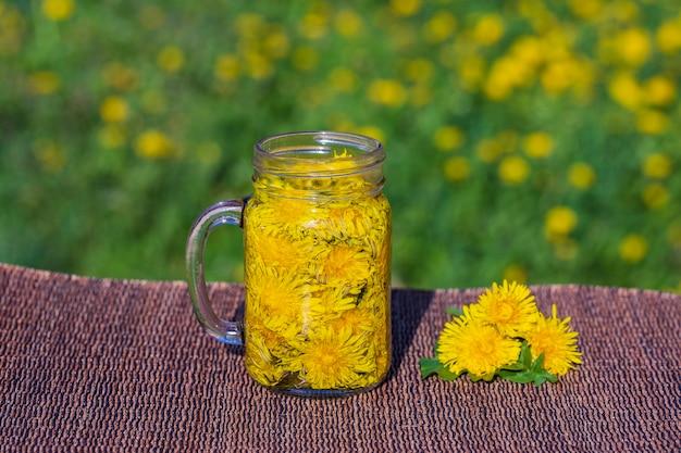 自然の背景、屋外、クローズアップのテーブルの上のガラスのマグカップでタンポポ黄色の花茶ドリンク。健康的な食事の概念