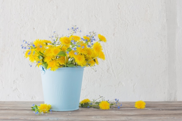 Dandelions and forget-me-nots on background white wall