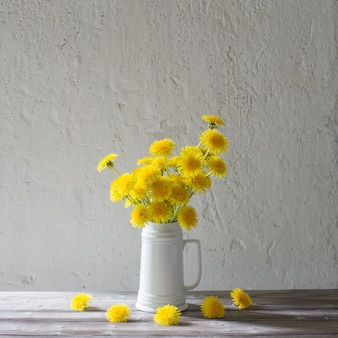 Dandelions in white jug on background white wall