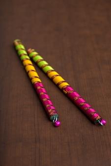 Dandiya палочки на коричневом фоне. раас гарба или дандия раас - традиционный народный танец штата гуджарат и раджастхан в индии.