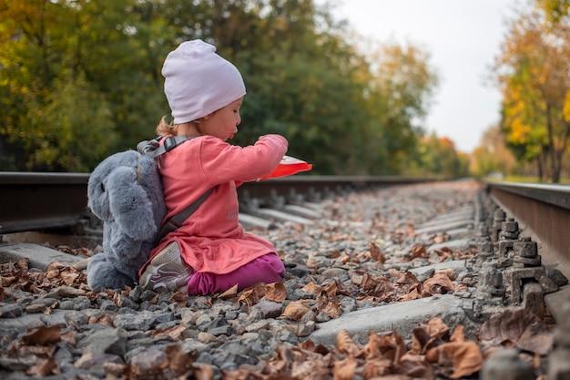 위험 게임. 철로에서 야외 마녀 돌을 노는 귀여운 어린 소녀.