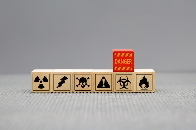 Danger icons on wooden cubes shape.