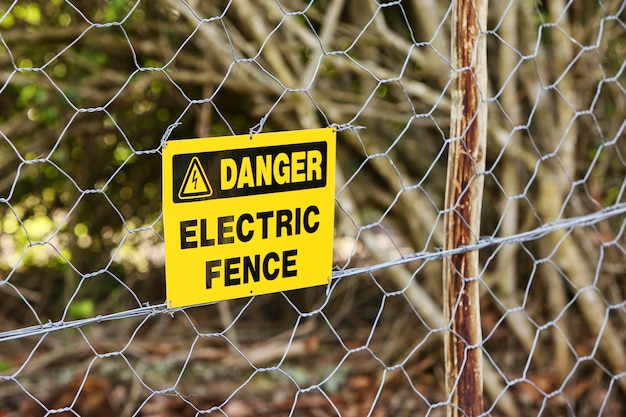 電気柵からぶら下がっている危険標識