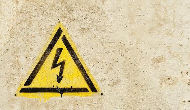高電圧電気の危険兆候。古い灰色のひびの入った背景に稲妻と黄色の三角形のハザードサイン。コピースペースのクローズアップ