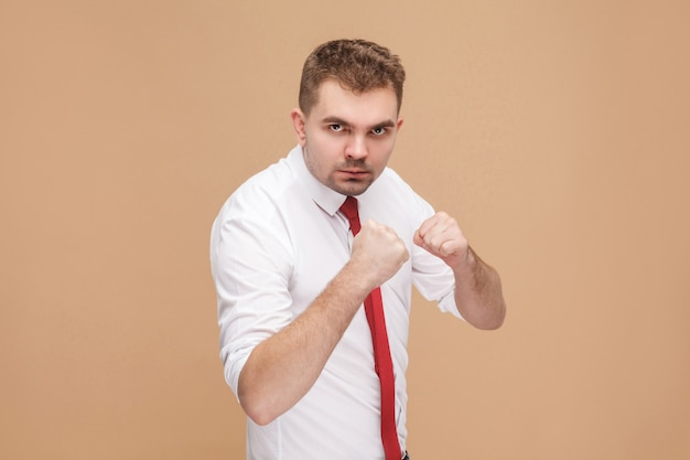 Danger and strong businessman showing boxing sign and ready to fight. business people concept, good and bad emotion and feelings. studio shot, isolated on light brown background