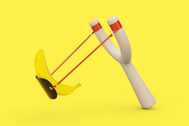 노란색 배경에 익은 노란색 바나나 과일이 있는 위험 나무 새총 장난감 무기. 3d 렌더링