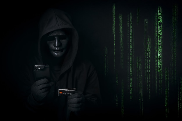 Dangerous anonymous hacker in hooded and mask use smartphone and credit card
