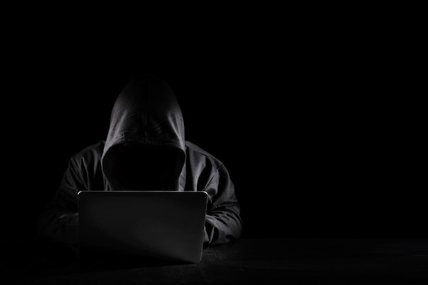 Dangerous anonymous hacker man in black hooded using computer, breaking into security data corporate server. he sitting, working on black background. internet crime, cyber attack security concept