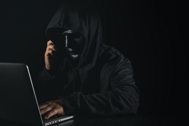 Dangerous anonymous hacker man in hooded and mask using computer and smartphone on black