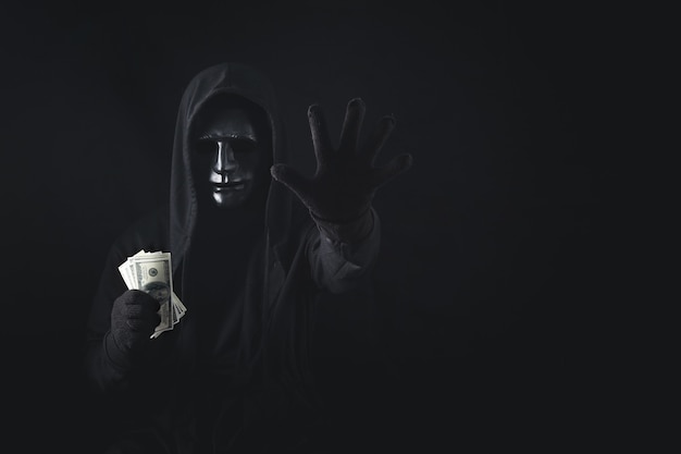 Dangerous anonymous hacker man in hooded showing stop gesture and holding banknote.