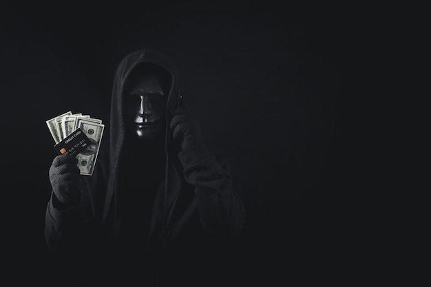 Dangerous anonymous hacker man in hooded use smartphone holding credit card and banknote
