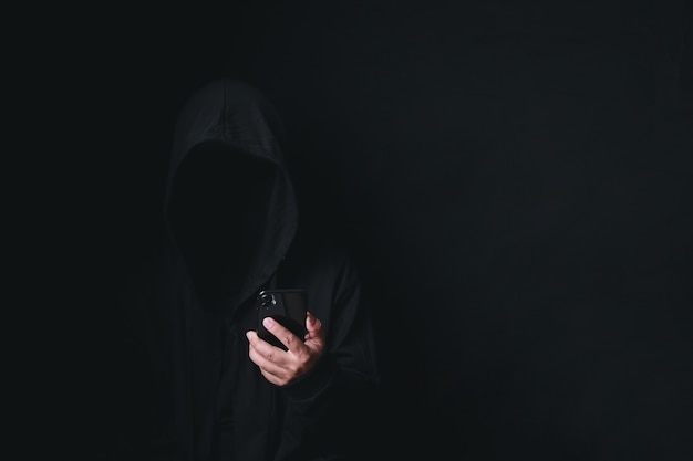 Dangerous anonymous hacker man in hooded use smartphone