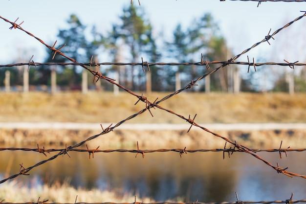 Опасная территория огорожена забором из колючей проволоки Premium Фотографии