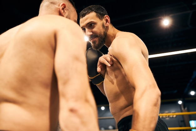 Dangerous boxer staring into his sparring partner eyes before the start of a fight