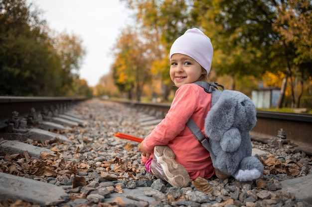 위험한 어린이 게임 개념. 쾌활 한 소녀는 혼자 철도 트랙에 앉는 다.