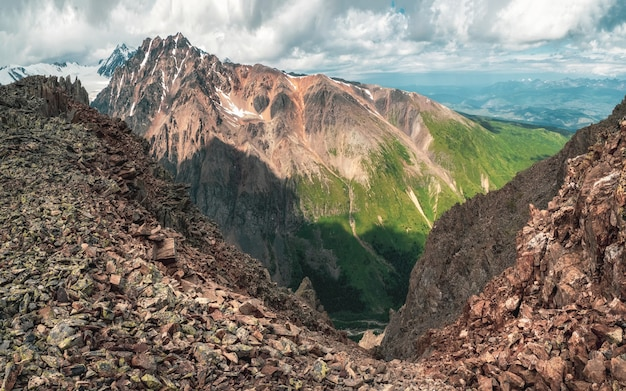 Dangerous couloir. colorful sunny green landscape with silhouettes of big rocky mountains and epic deep gorge.