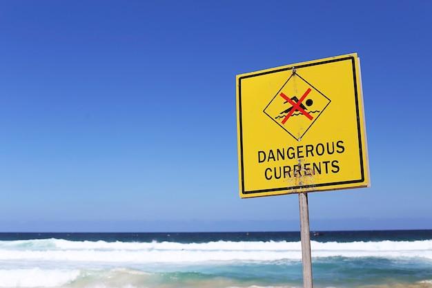 화창한 날에 해변에 위험한 전류 기호