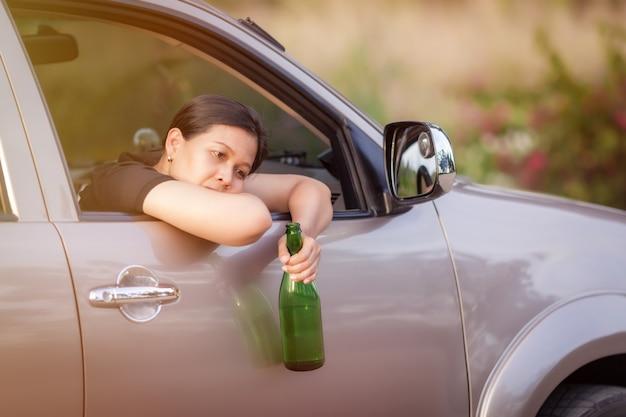 危険な運転-若い女性がビールを飲み、車を運転し、車内でアルコールを飲み、交通事故の概念